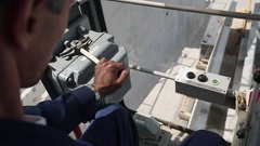 Workers hand contols the crane. Camera closeup inside the cabin. Stock Footage