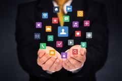 Businessman holding colorful applications Stock Photos