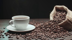 Beautiful composition the Cup of hot coffee and coffee beans on table, Dolly Stock Footage