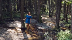 Young girl with white skin, on a stream with clear water in a blue dress is Stock Footage
