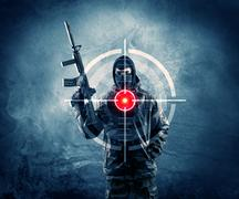 Masked terrorist man with gun and laser target on his body Stock Photos