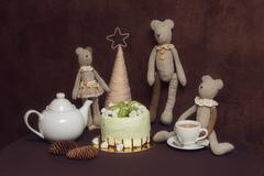 Teddy bears, green pistachio cake with macaroons and marshmallows Stock Photos