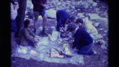 1981: group of people sitting and standing, collecting things from the ground Stock Footage