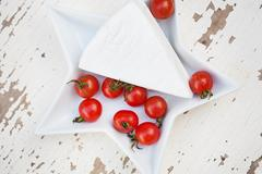 Wooden background plate of brie cheese and cherry tomatoes close-up Stock Photos