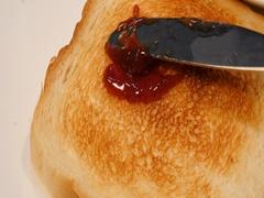 Spreading strawberry jam on bread Stock Footage