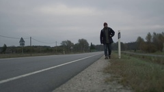 Casualy Dressed Traveler Walking along the Highway at a Cloudy Day. Stock Footage