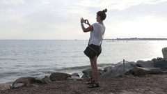 Caucasian blond female filming beach scenery before sunset Stock Footage