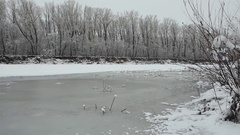 Winter landscape with snowy trees, beautiful frozen river and bushes at sunset Stock Footage