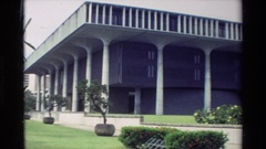 1981: a large concrete building looms over a garden of yellow roses HAWAII Stock Footage
