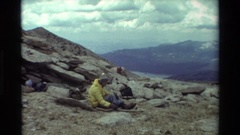 1981: man wearing yellow shirt and cap sitting on a stony ground BRITISH Stock Footage