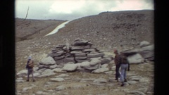 1981: several people wearing packs passing a large pile of rocks BRITISH Stock Footage
