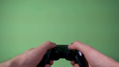A man with a joystick on a game console plays on a green background Stock Footage