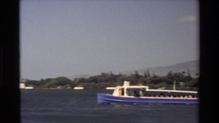 1981: panning views of boat passing nearby the pearl harbor memorial and flag. Stock Footage