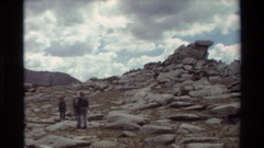 1981: a group of three men walking side by big rock carvings. BRITISH COLUMBIA Stock Footage