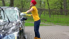 Pretty woman in colorful clothes washing black automobile car with soapy sponge Stock Footage
