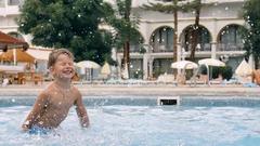 Young boy kid child splashing in swimming pool having fun leisure activity. Stock Footage
