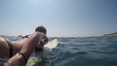 SLOW MOTION HALF UNDERWATER: Fit young female surfer paddling out on sunny day Stock Footage