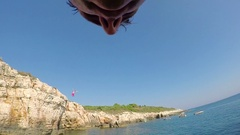 FPV, SLOW MOTION: Joyful man jumping head first from tall dangerous rocky cliff Stock Footage