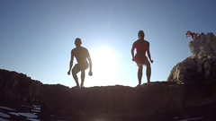 SLOW MOTION CLOSE UP: Joyful man and woman jumping off rocky edge into the ocean Stock Footage