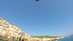 FPV, SLOW MOTION: Active man jumping head first from tall dangerous rocky cliff Stock Footage