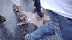 Feet in sandals legs with shoes walking over Bruce Willis star Hollywood Blvd Stock Footage