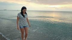 Slim brunette girl walks on the beach enjoying and inspired by sunrise. Stock Footage