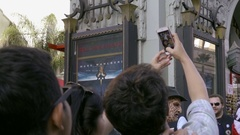 Young man taking picture with smartphone of Chinese Theater with friends in LA Stock Footage
