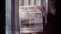 1982: granny reading old newspaper SACRAMENTO CALIFORNIA Stock Footage