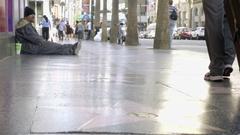 Homeless man sitting on street nodding tourist with stars on Hollywood Blvd LA Stock Footage