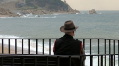 Elderly Retired Pensioner Looks Out to Sea Stock Footage