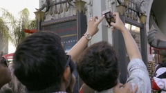Friends taking smartphone picture of Chinese Theater sign on Hollywood Boulevard Stock Footage