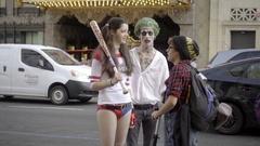 Joker Harley Quinn actors in costume talking on street Hollywood Boulevard LA Stock Footage