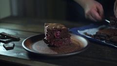 Chocolate cake pieces. Man hand put piece of chocolate cake on plate Stock Footage