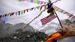 View of american and prayer flags waving on wind in Everest base camp. Himalaya Stock Footage