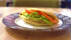 Tomato, lettuce and chicken sandwich on the plate Stock Footage