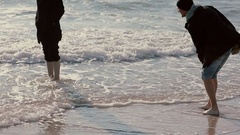 Two young guys are soaking their feet in the waves of the sea smiling and Stock Footage