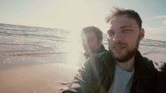 Two young goofy guys with beards are standing on a sandy beach trying to take a Stock Footage