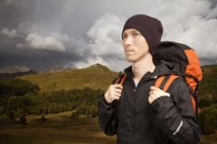 Hiker with backpack walking along a mountain terrain Stock Photos