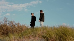 Two young men are walking down from a sandy dunes chatting and smiling Stock Footage