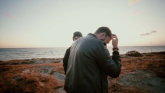 At sunset two young guys are standing on a sandy beach and looking right at the Stock Footage
