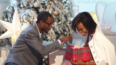 African couple have a good time near New Year tree. Man present a gift to woman Stock Footage