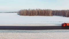 Many trucks drives on snow highway in sunsets Stock Footage