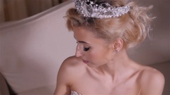 Portrait of young beautiful woman with long blond hair. Blonde bride with crown Stock Footage