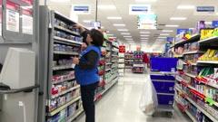 Clerk stocking medicine on shelf at pharmacy section inside Walmart store Stock Footage
