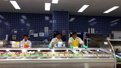 Seafood clerk stocking fish and chatting to co-worker inside T&T Stock Footage