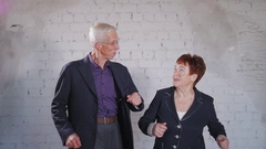 Happy senior couple in love dancing and smiling in studio. Old wife and husband Arkistovideo