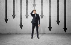 Sad businessman in frustrated pose, standing on background of many black arrows Stock Photos