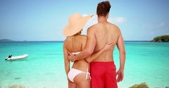 Millennial couple standing together looking at the clear water Stock Footage