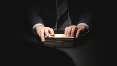 Bribe: Businessman waits, touches a money bundle and gives it - two person Stock Footage