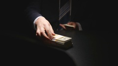Bribe: Businessman counts a money bundle on a table - Two person Stock Footage